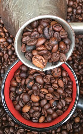 a pile of coffee beans in turk and on the table. Coffee texture and background image. Foto de archivo