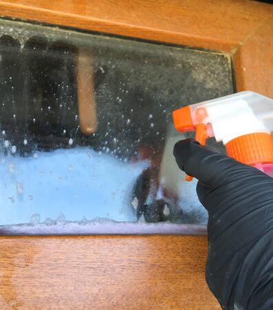 A woman in a black glove cleans a window with a spray bottle. House cleaning. Washing dirty window detergents in summer. Foto de archivo