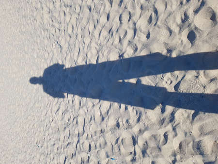 The shadow of a person with long legs on the sand at a beach