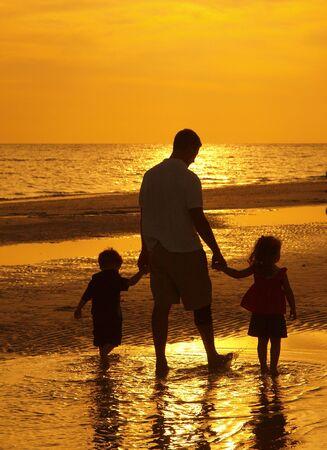 ni�os caminando: Padre y los ni�os caminando en la playa puesta de sol Foto de archivo
