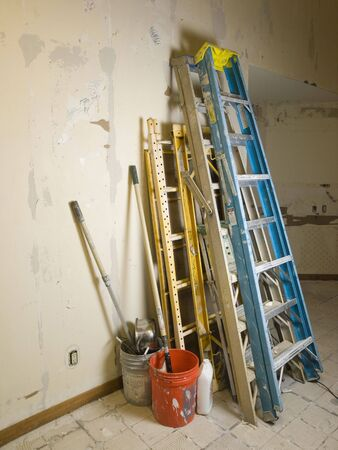 messy kitchen: Photo image of ladders and scafolding leaning against a wall in a gutted kitchen that is under renovation constuction. Stock Photo