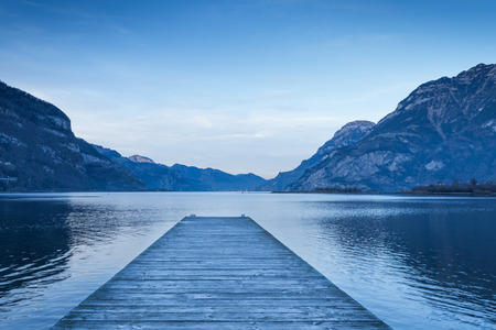 Background as epic mountain landscape.  Lake at sunset  with wooden pier.
