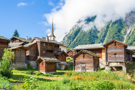 sunburnt: Sun-burnt chalets, green forests and meadows in Valais, Swiss Alps traditional village Blatten Stock Photo