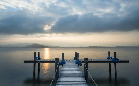 long lake: Wooden pier on the lake. Fog. Long exposure. Stock Photo