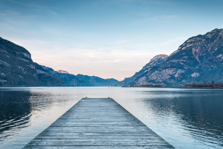 Background as epic mountain landscape.  Lake at sunset  with wooden pier . Stock Photo