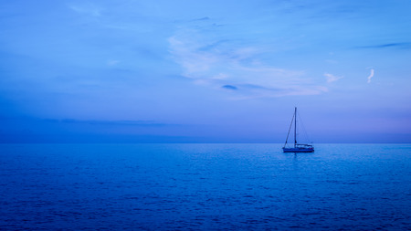 skie: Sea surface is painted in ultramarine and blue colors sunset. Clear skie with some clouds. Stock Photo