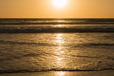 Sun sets over horizon of ocean. Surf on sandy beach. Sky, water and shore in the evening painted in orange, gold color. Stock Photo