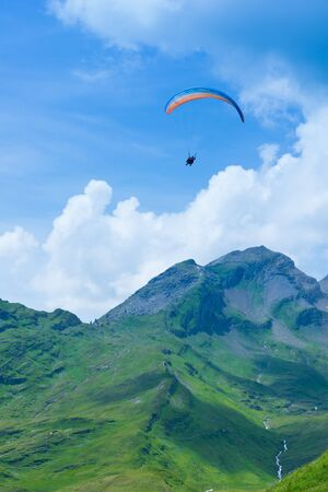 schweiz: parasailing over the mountains among the clouds