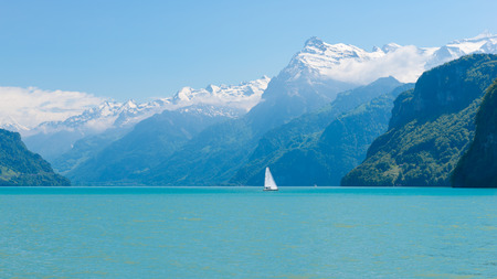 Sommer: Magnificent panorama of mountains with snowy peaks. On  surface of lake sailboat sails. Cloudless blue sky and a few clouds in the mountains