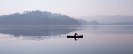 Man floating in a boat. Fog over the lake, mountains reflected in the water