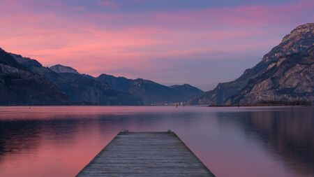 long lake: Spectacular sunset over lake in the mountains. Gorgeous colors of clouds reflected in water. long exposure Stock Photo