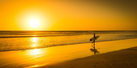 oceana: Surfer with board on the sand beach Oceana. Bright sunset on the horizon. Stock Photo