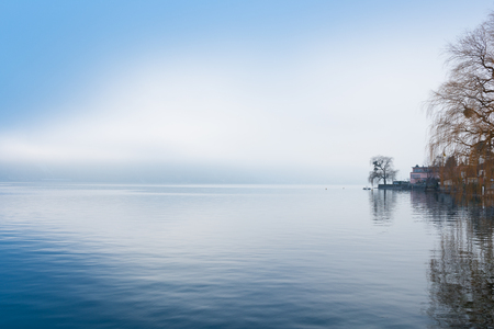 Winter landscape with fog and clouds. Tree with autumn foliage remained reflected in water of  lake.