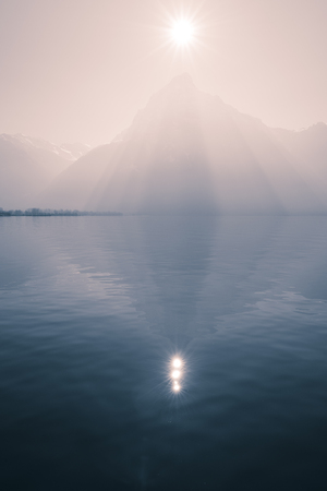 Sunrays over the top of the mountains reflected in the lake. Play of light and shadow creates volume pyramid shape.