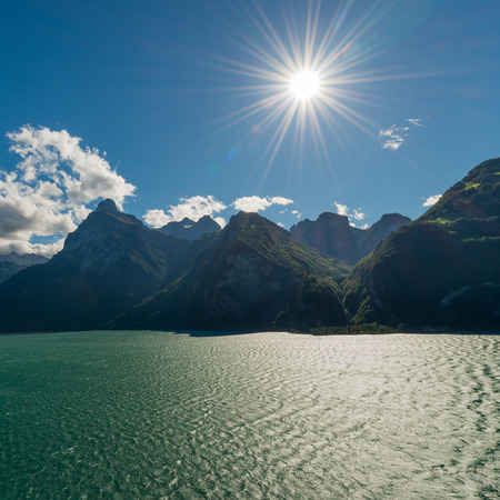 flair: Sun over mountain peaks. Bright rays with lens flair effect. Landscape of a mountain lake in autumn.