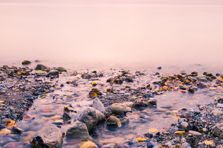 long lake: Autumn landscape on the lake. On the shore are colored stones and fallen leaves.  Long exposure