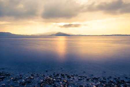 long lake: Autumn evening over the lake. Rays of sun shining behind the clouds. Long exposure. Stock Photo