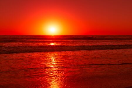 san rays: Setting sun over the Pacific ocean colors the sky and waves in red color.