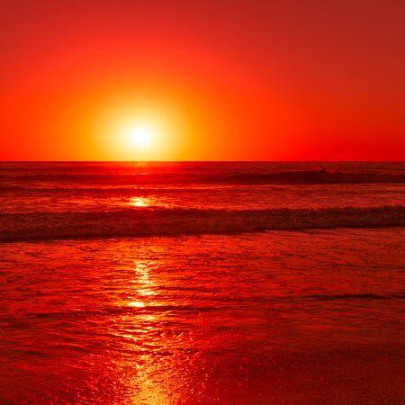 태평양을 일출하는 것은 하늘과 파도를 붉은 색으로 물들입니다.