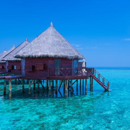 Panorama of tropical island resort with overwater bungalows. Blue sky with a few clouds. Turquoise water of lagoon.