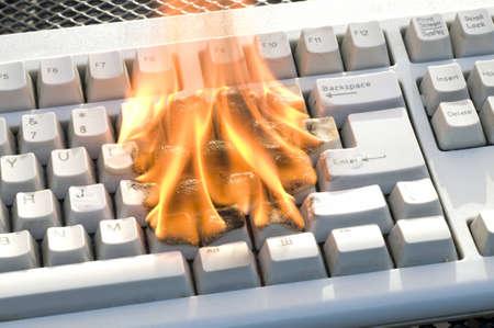 virus informatico: teclado del ordenador en el fuego Foto de archivo