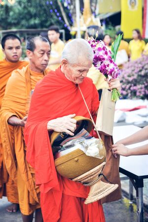 religious clothing: Offering food to the monk.