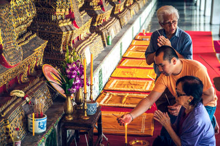 venerate: Thai people praying to the image of Buddha. Editorial
