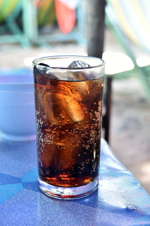 carbonation: glass of cola with ice on the table in restaurant
