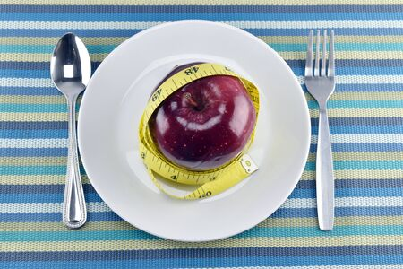 flatware: Red apples, measuring tape with Flatware in dish on napery concept  for healthy diet and body weight control. Stock Photo