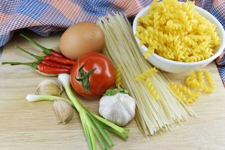 fusilli spaghetti garlic chili onion egg and tomato on  wooden background. photo