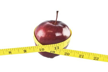 Red apple and yellow measuring tape concept for healthy diet and body weight control. photo