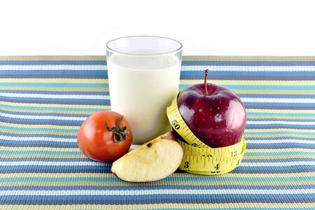body milk: Red apples, measuring tape, glass of milk and tomato in on napery concept  for healthy diet and body weight control.