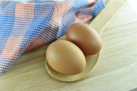 Two egg in wooden spoon and fabric on wooden background photo