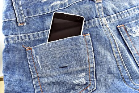 Black phone in your pocket blue jeans background photo