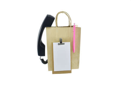 pluma y papel: Brown paper shopping bag, pen, paper and  telephone on white background with clipping paths Foto de archivo