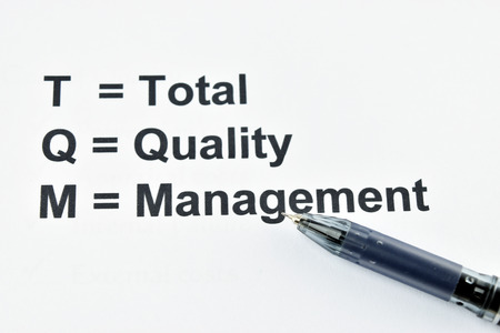 pen quality: TQM total quality management with back pen on white background