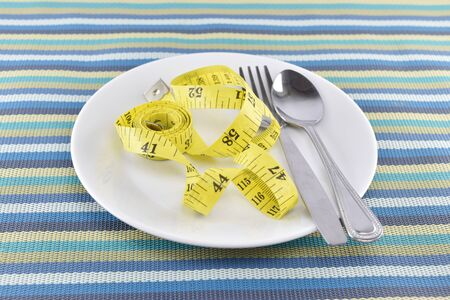 weight control: yellow measuring tape with spoon and fork on dish concept for healthy diet and body weight control.