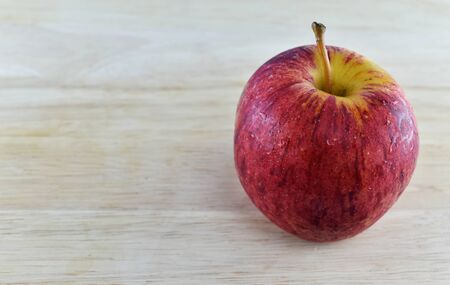 weight control: Red apple  on wooden background concept for healthy diet and body weight control. Stock Photo