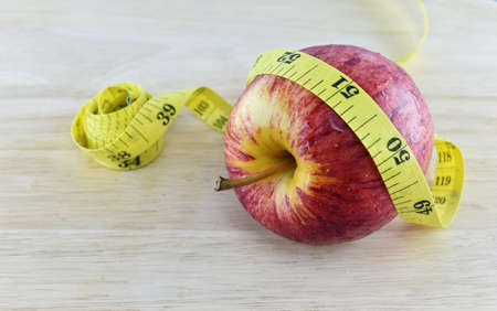 weight control: Red apple and yellow measuring tape concept for healthy diet and body weight control.