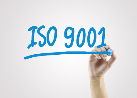 women hand writing ISO9001 on gray background for business strategy and used in manufacturing.