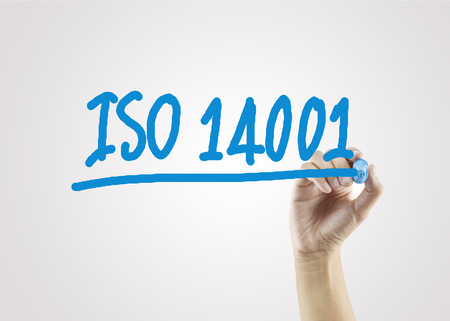 women hand writing ISO14001 on gray background for business strategy and used in manufacturing. Stock Photo