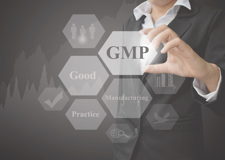 Bedrijfsvrouw die presentatiebetekenis van GMP-concept (Goede Productiepraktijk) een principe op zwarte achtergrond tonen. Idee voor gebruik in productie en training.