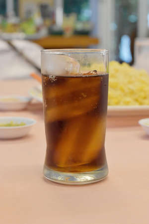 Cola in glass with ice on table in restaurant Stock Photo