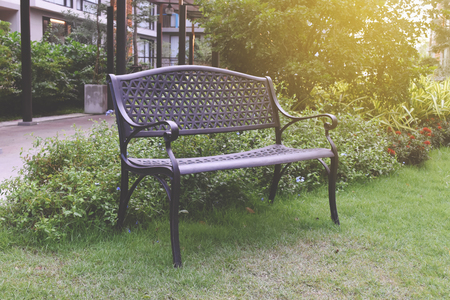 Decorative bench in public area for relaxing on grass background.  Banco de Imagens