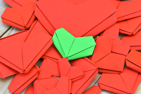 Difference green paper heart shape put on many red paper heart shape background. Concept for Valentines Day background, wedding and take care of your health.