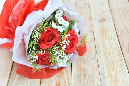 Red roses bouquet put on wooden background. Concept for Valentines day or Wedding. Banco de Imagens