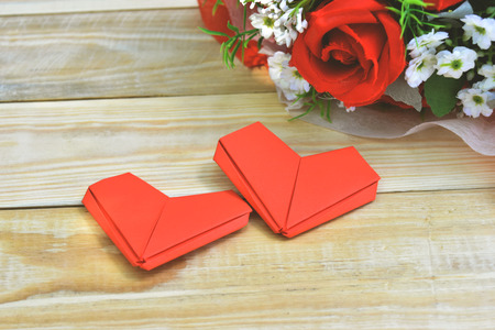 Red roses bouquet and paper hearts shape put on wooden background. Concept for Valentines day, Birthday or Wedding. Vintage or light sunshine to the bouquet.