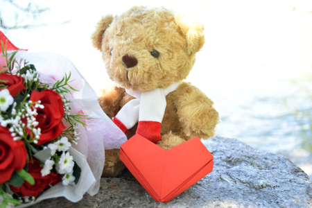 Cute Teddy bear with paper red heart, red roses bouquet on old stone and sea background. concept of love Valentines Day, Friendship, Family and Wedding.
