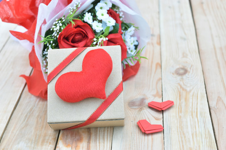 Red roses bouquet, gift box and red hearts shape on wooden background. Concept for Valentines Day, Birthday or Wedding.