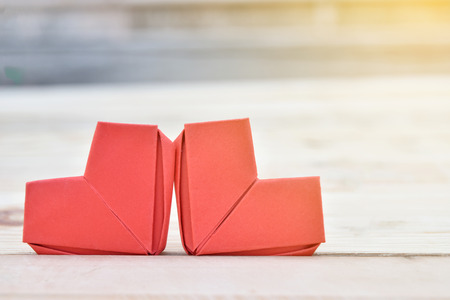 Couple red paper hearts shape put on wooden background. Concept for in Love, Valentines Day, Birthday or Wedding.